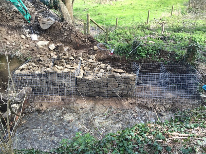 Gabion baskets were installed on solid rock base and back filled with stone and topped with soil. North Devon