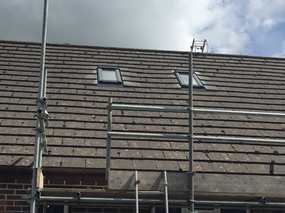 Scaffold was erected as a crash deck, and works were carried out from a roofing ladder. Velux flashing kits were fitted to the windows and the original tiles cut and refitted. in North Devon