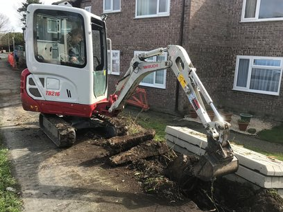 Excavation of concrete and bushes was completed with mechanical help.