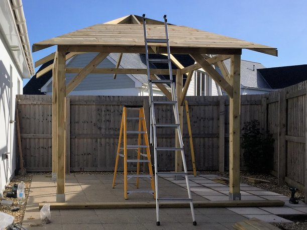 Gazebo erected on supporting posts with roof being assembled