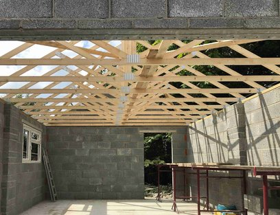 Garage roof truss construction completes, window installed. North Devon