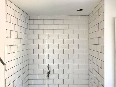 Brick bond tiling using rectangle tiles installed in the new shower area. North Devon