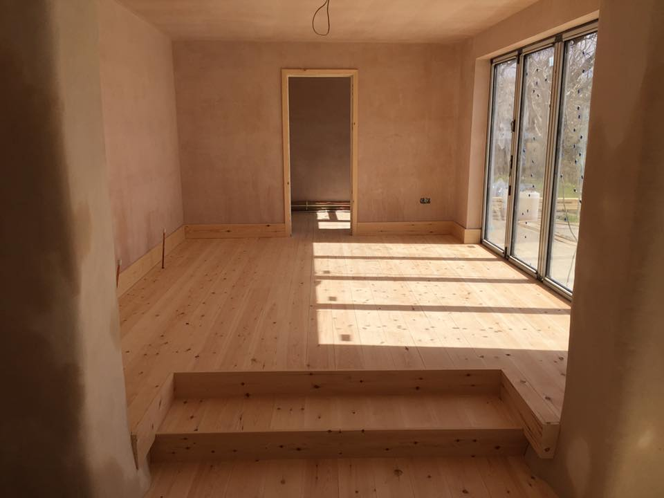 Pine wooden floor fitted, with some tight scribes around the plaster walls. North Devon